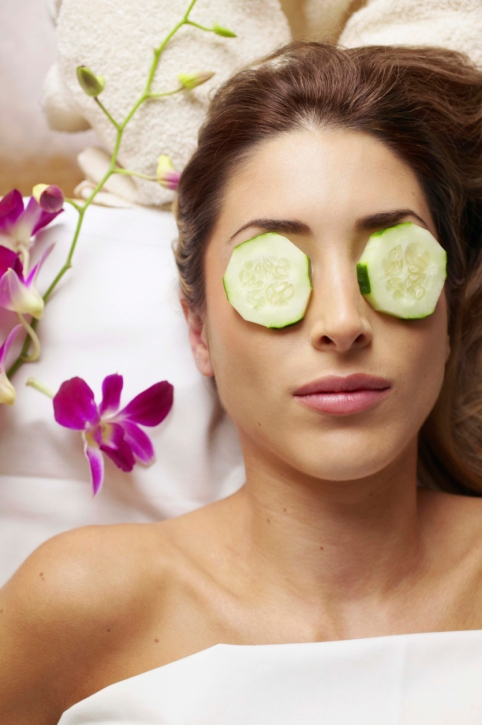 Woman with cucumber slices on eyes in spa